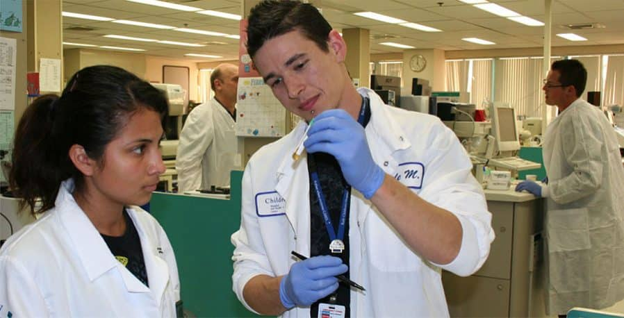 Male doctor showing a woman student a test tube